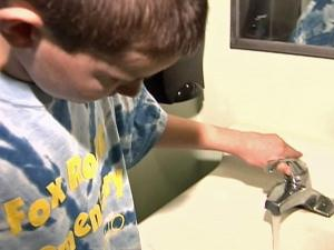 A Fox Road Elementary student checks the flow on a school faucet.