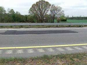 Black patches cover large cracks and pot holes along Interstate 795.
