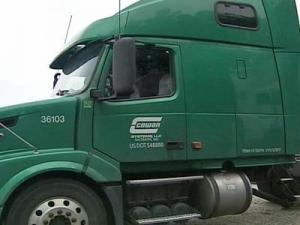 The 2006 Volvo truck cab is hunter green with a white Cowan Systems logo and Maryland registration 541F29.
