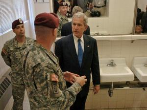 President George W. Bush speaks to Col. Martin Schweitzer as he gets a tour of the latrine in the highly publicized Charlie Co., 2nd Battalion, 508th Parachute Infantry Regiment's barracks.  (Photo by Stephanie Bruce / Fayetteville Observer)