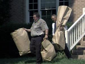Authorities carry brown packages from the home of Nancy and Brad Cooper on the morning of July 16, 2008.