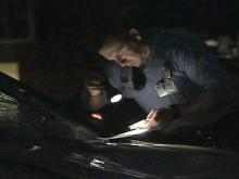 A police officer reads some documents while standing near a vehicle involved in a crash Friday morning.