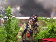 A firefighters pauses in front of a large blaze at the former Milliken textile plant in Robbins on Aug. 17, 2008. (photo by Lynn Pennington)
