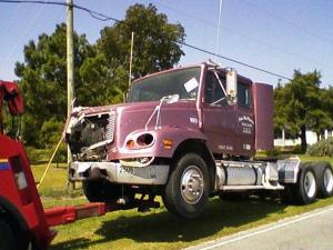 A tow truck hauls away the tractor unit of an 18-wheeler that crashed into a farm truck as it was carrying eight workers on N.C. Highway 11 on Monday, Sept. 1, 2008.