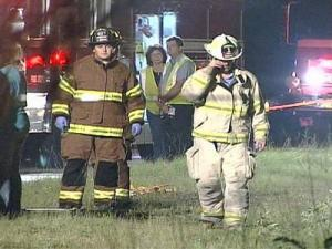 Emergency crews work at the scene of a fatal crash that killed two young men.
