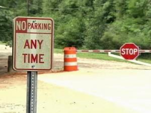 Signs and a barricade prevent visitors to Umstead State Park from parking on Graylyn Drive off Ebeneezer Church Road.