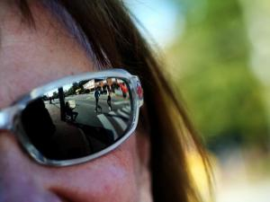 Runners are reflected in Eraine Oakley's sunglasses as they head towards the finish.