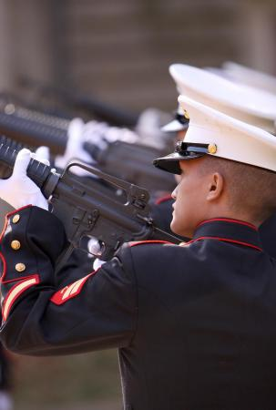 A line of Marines firing during the ceremony.