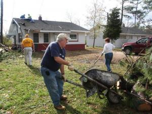 Volunteers with the First Baptist Church Disaster and Emergency Services group help clean up after a tornado damaged homes on Dixon Street in Elm City.