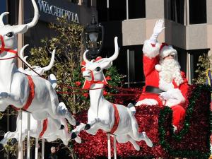 Santa Claus waves to kids young and old as he makes his way down Fayetteville St.