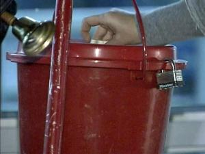 A person slips a donation into the Salvation Army kettle as a bell ringer stands by.