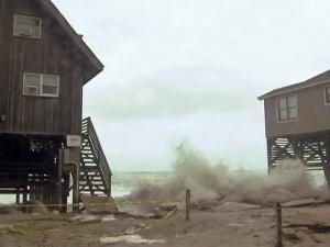 Waves smash up on the sand between two beachfront homes on the North Carolina coast during a storm.