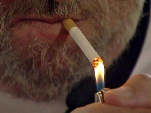 A man lights up a cigarette.
