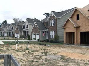 Unfinished homes sit next to occupied residences in the Villages at Beaver Dam development in Knightdale.