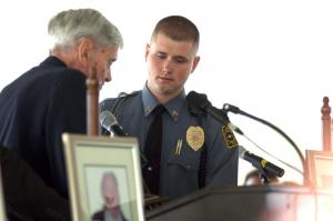 Community member Bill Stutts gives a plaque to Cpl. Justin Garner in honor of his service on the day of the shooting.