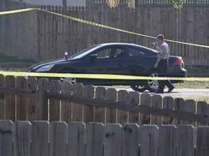 A police officer walks in front a parked car on Corydon Court, where a man's body was found lying face-down in the Battle Ridge at Chastain community, off Barwell Road, early Tuesday, May 12, 2009.