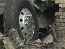 Truck strikes house, man along road
