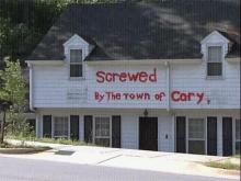 A Cary man could face a fine for the spray-painted protest he has on his Maynard Road house.