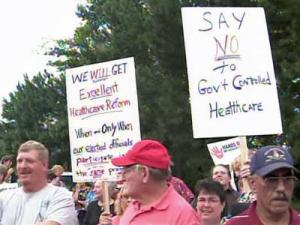 People hold up signs outside of a town hall meeting on health care reform Wednesday, August 12, 2009, at Central Carolina Community College in Lillington.