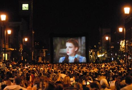 """THURSDAY: An outdoor showing of the film, """"The Wizard of Oz"""" draws more than 2,000 people to downtown Oconomowoc, Wis., for a 70th anniversary presentation of the Hollywood classic. The city was the site of the film's world premiere in 1939. (AP Photo/Watertown Daily Times/John Hart)"""
