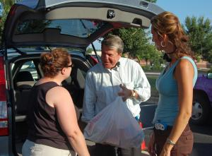MIX 101.5 host Lynda Loveland and WRAL Anchor David Crabtree thank Heide Cassimatis for donating items to the BackPack Buddies food drive on Aug. 20, 2009. Cassimatis said her daughter never has to worry about going hungry, so she wanted to help children who are less fortunate.