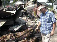 Chad Honeycutt surveys the damage to his tobacco crop after an Aug. 26, 2009, fire destroyed four tobacco barns and a warehouse on his in-laws' farm.