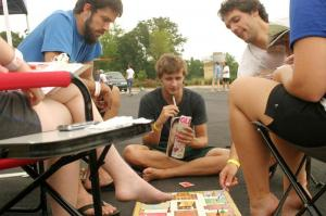 """Drew Burlick, David Instoe and Andrew Wallace, all of Charlotte, passed the time with a game of Clue.  """"It's really just about having a good time with your friends,"""" Instoe said."""