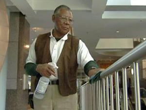 George Height, of MG Capital Maintenance, spends his days scrubbing door handles, elevator buttons and other places in the building at 434 Fayetteville St.