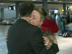 Ryan Allis gives his girlfriend, Jessica Shorland, a hug and some flowers after arriving at Raleigh-Durham International Airport on April 22, 2010. Allis had been stranded overseas for four days by volcanic ash that brought air travel in much of Europe to a standstill.