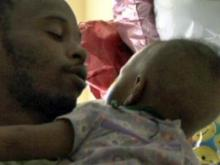 Demarco Garner holds his daughter, Jaliyah, while she is being treated at a Greenville rehabilitation center on Sept. 7, 2010.