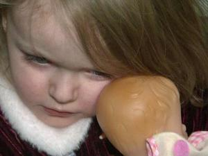 Shania Elsik, 2, snuggles a doll, a Christmas gift from a neighbor.