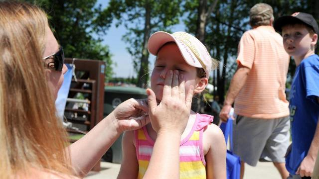 Tami (left) of Fayetteville applies sunscreen to her daughter Annie during the annual Dogwood Festival in Fayetteville, NC on April 30, 2011. (Photo by Lance King)
