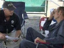 A FEMA agent talks with Dunn resident Wille Wrench, right, about damage to his home caused by an April 16, 2011, tornado.