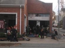 Chapel Hill police defended the force used in arrests at an illegal encampment inside an unoccupied building downtown Monday during a town council meeting, saying riot gear and assault rifles were necessary to raid the building.