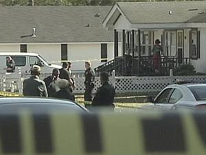 Fayetteville police officers search for evidence at 288 Ingram St., where two people were killed and three others injured during a home break-in on Saturday, Nov. 26, 2011.
