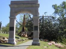 Large stone arch at Oakwood Cemetery in Raleigh with mangled trees in background. Days after the tornadoes of April 16, 2011.