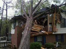 Tree on a house on N. King Charles Street in Raleigh. Days after the tornadoes of April 16, 2011.
