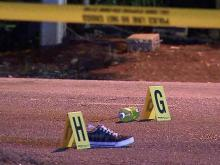 Police evidence markers stand next to a shoe and soda bottle in New Bern Avenue where a car struck and killed Simmie Earl Brown, 24, as he crossed the road Monday, May 28, 2012.