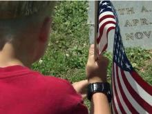 Families make tradition of placing flags on vets' graves