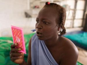 A woman looks at her newly formed mouth in the mirror after undergoing surgery on her cleft lip. (Photo courtesy of Samaritan's Purse)
