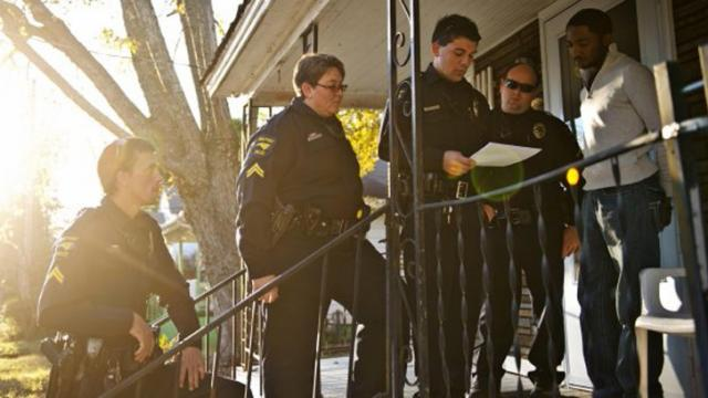 High Point police Officer Perks Shepherd reads a search warrant to man who was later arrested. Police were investigating reports of drug dealing in the area.