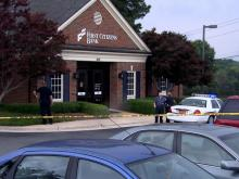 Crime scene tape surrounds the First Citizens Bank branch at 1825 Kildaire Farm Road after an armed robbery on June 24, 2014.