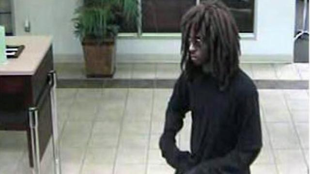 Investigators are searching for an armed man whose wig disguise fell off as he robbed a State Employees Credit Union in Wilson on July 7, 2014.