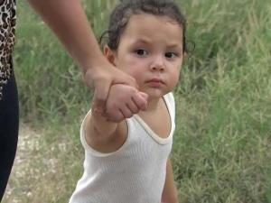 A woman and a child cross the border from Mexico to the U.S.