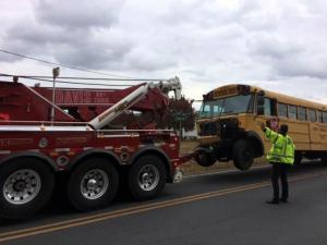 A Robeson County school bus is towed away on Nov. 17, 2014, hours after it was involved in a head-on collision on Wire Grass Road, south of Lumberton, in which four people in a car were killed.