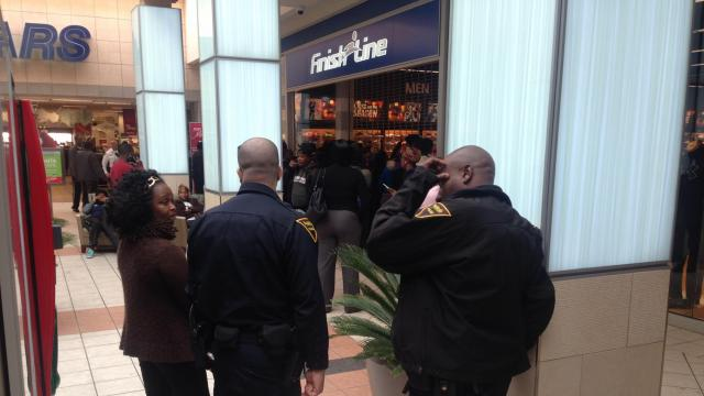 Fayetteville police officers provide security as a crowd gathers to wait for the sale of a popular brand of basketball shoes at Finish Line at Cross Creek Mall on Dec. 17, 2014.