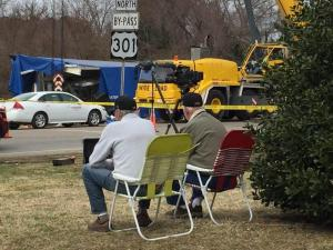 Gerald Wright, left, and a friend, brought their lawn chairs to sit and watch Tuesday as crews cleaned up the wreckage of an Amtrak train crash in Halifax County.