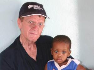 Philip Dail visits with a child at an orphanage in Haiti.