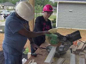 Michelle Pavliv helps a fellow volunteer with Habitat for Humanity of Wake County.