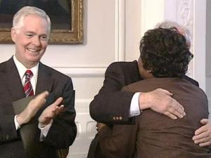 Gov. Mike Easley looks on as Dr. Craig Phillips, former superintendent of the Winston-Salem school district hugs one of 11 former students who were the first black students to enter all-white public schools.